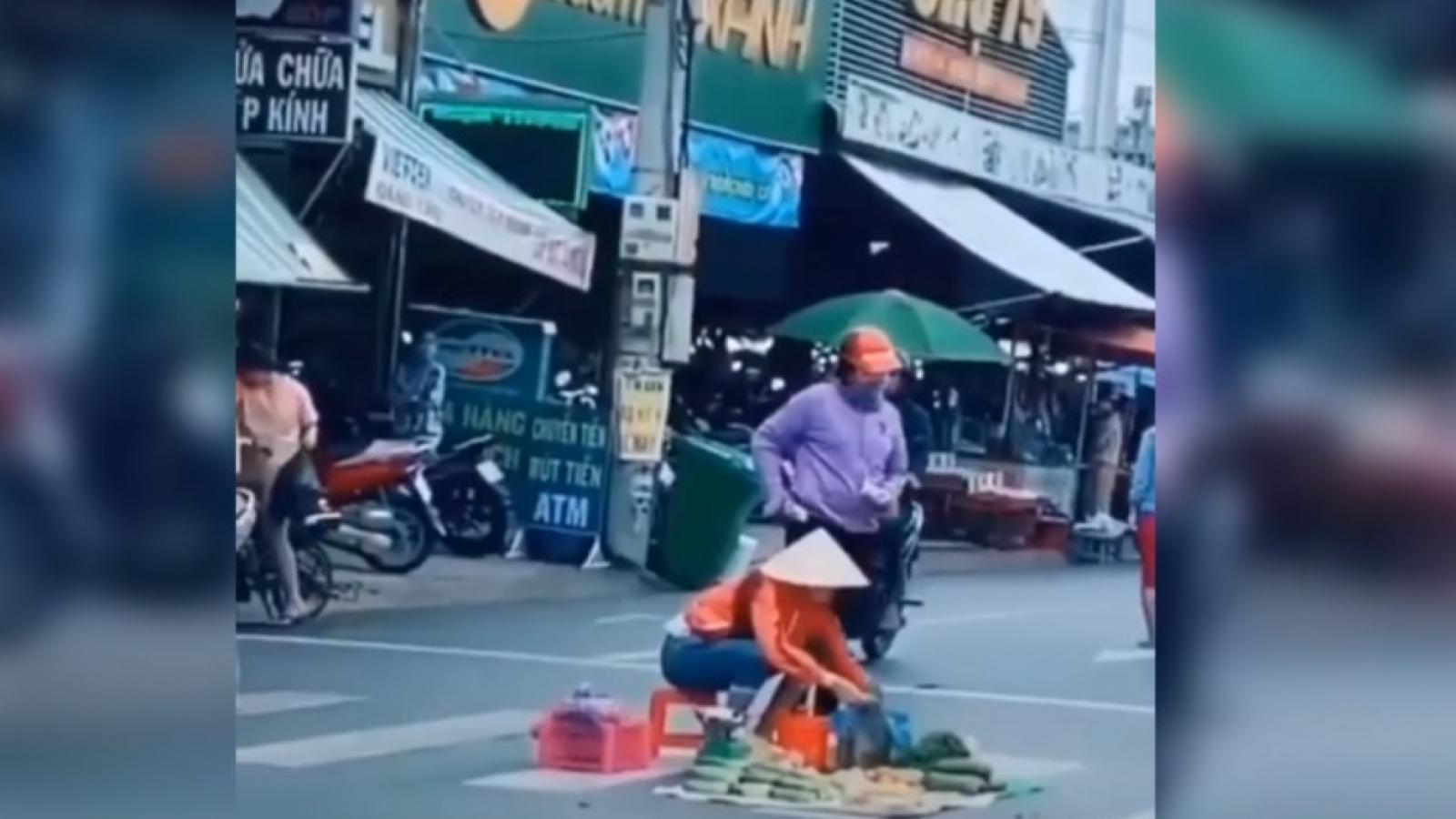 Người phụ nữ ngồi bán trái cây giữa lòng đường mặc xe cộ qua lại