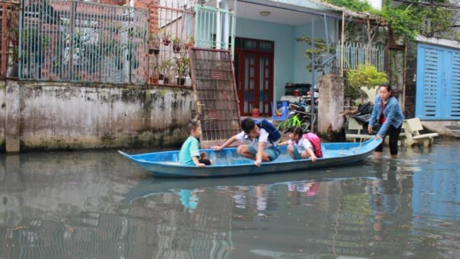 Ảnh: Triều cường liên tục đạt đỉnh, người Sài Gòn dùng xuồng đưa con đi học