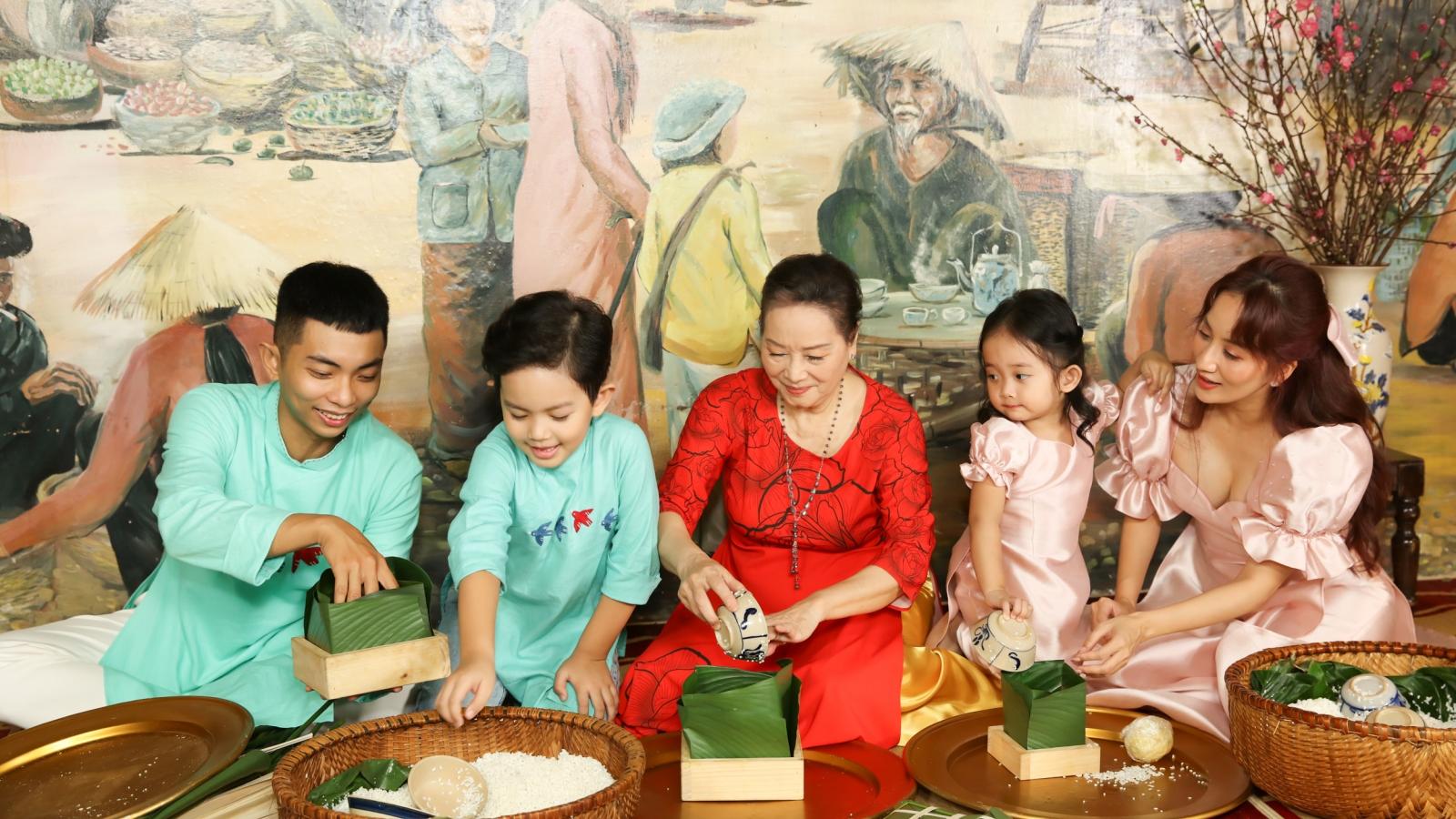 Vợ chồng Khánh Thi dạy hai con gói bánh chưng trong MV ngày Xuân