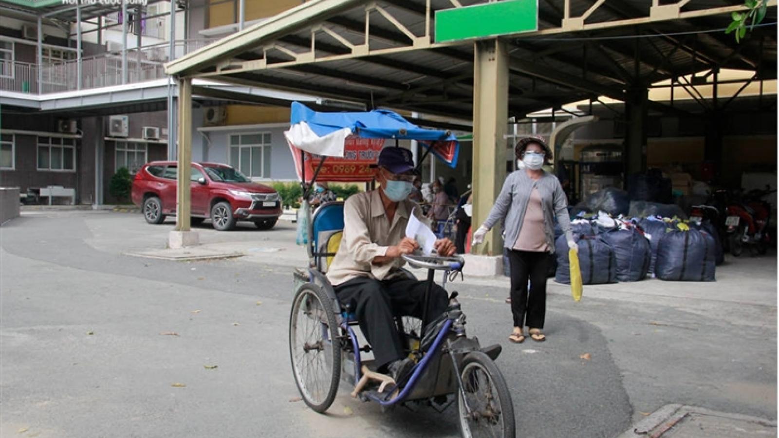 Người già mắc bệnh nền ở TP.HCM ngồi xe lăn, chống gậy đi tiêm vaccine COVID-19