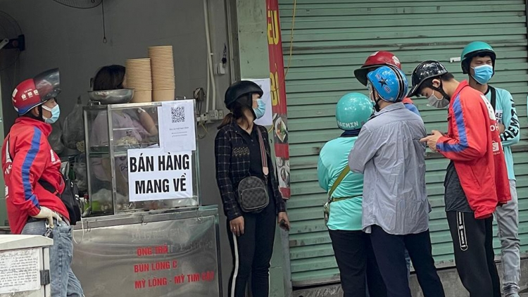 Locals apply pandemic counter measures at eateries in Hanoi
