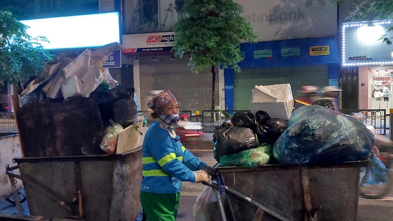 Nữ lao công miệt mài quét rác trong đêm lạnh đầu đông