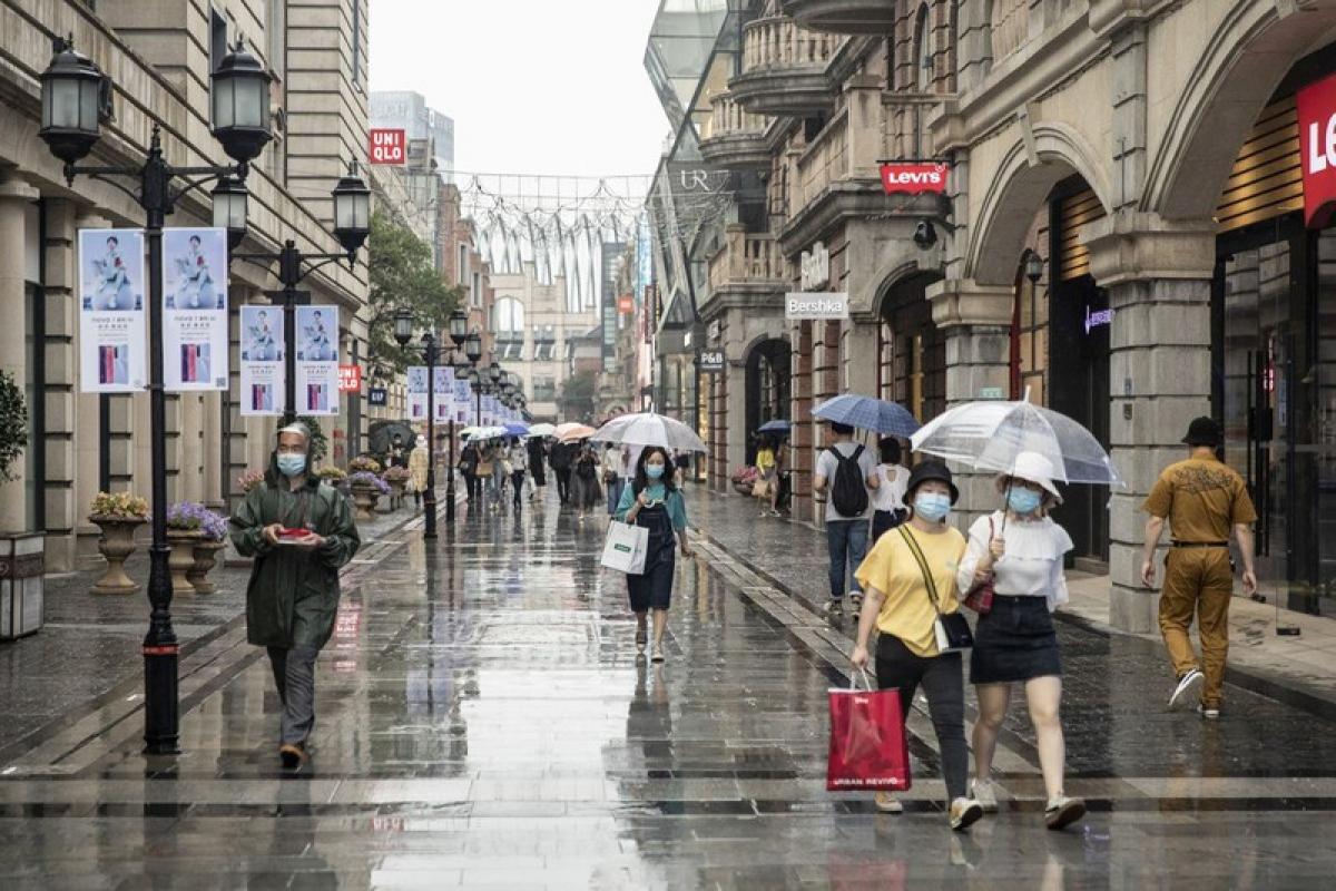 Những người đi bộ trên một con phố ở thành phố Vũ Hán ngày 30/4. Ảnh: Bloomberg