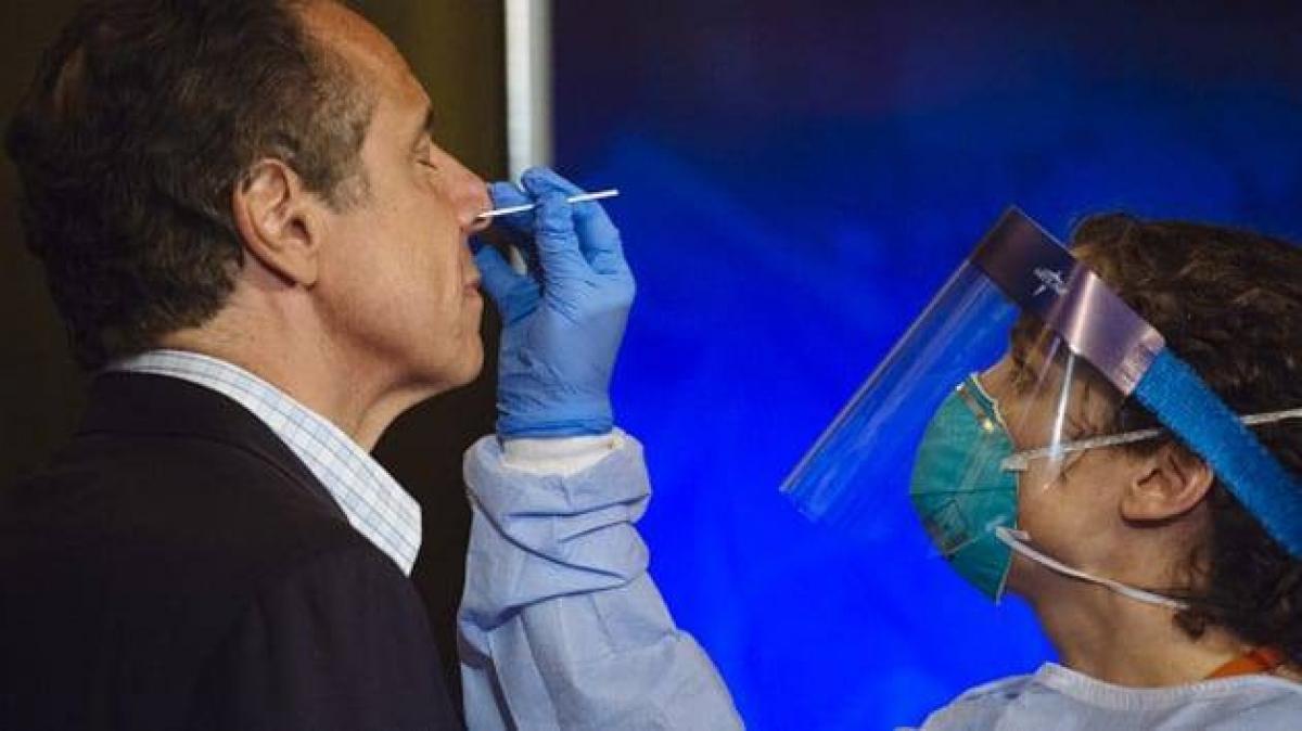 Bác sĩ trong bộ đồ bảo hộ lấy dịch mũi của ông Andrew Cuomo để lấy mẫu xét nghiệm. Ảnh: Bloomberg.
