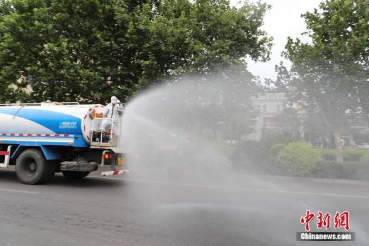 Phun thuốc khử trùng tại khu vực gần doanh nghiệp có nhiều ca Covid-19 ở Đại Liên hôm 23.7. Ảnh: Chinanews