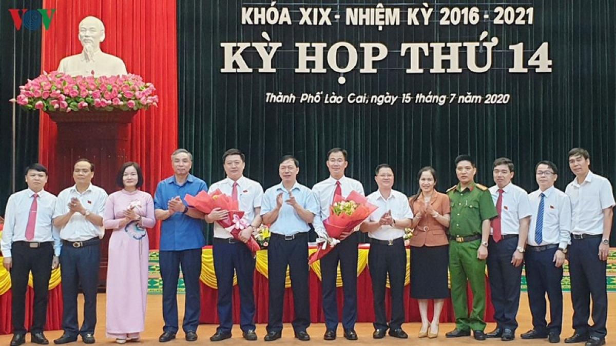 2 tân Phó Chủ tịch UBND thành phố Lào Cai nhận hoa chúc mừng.