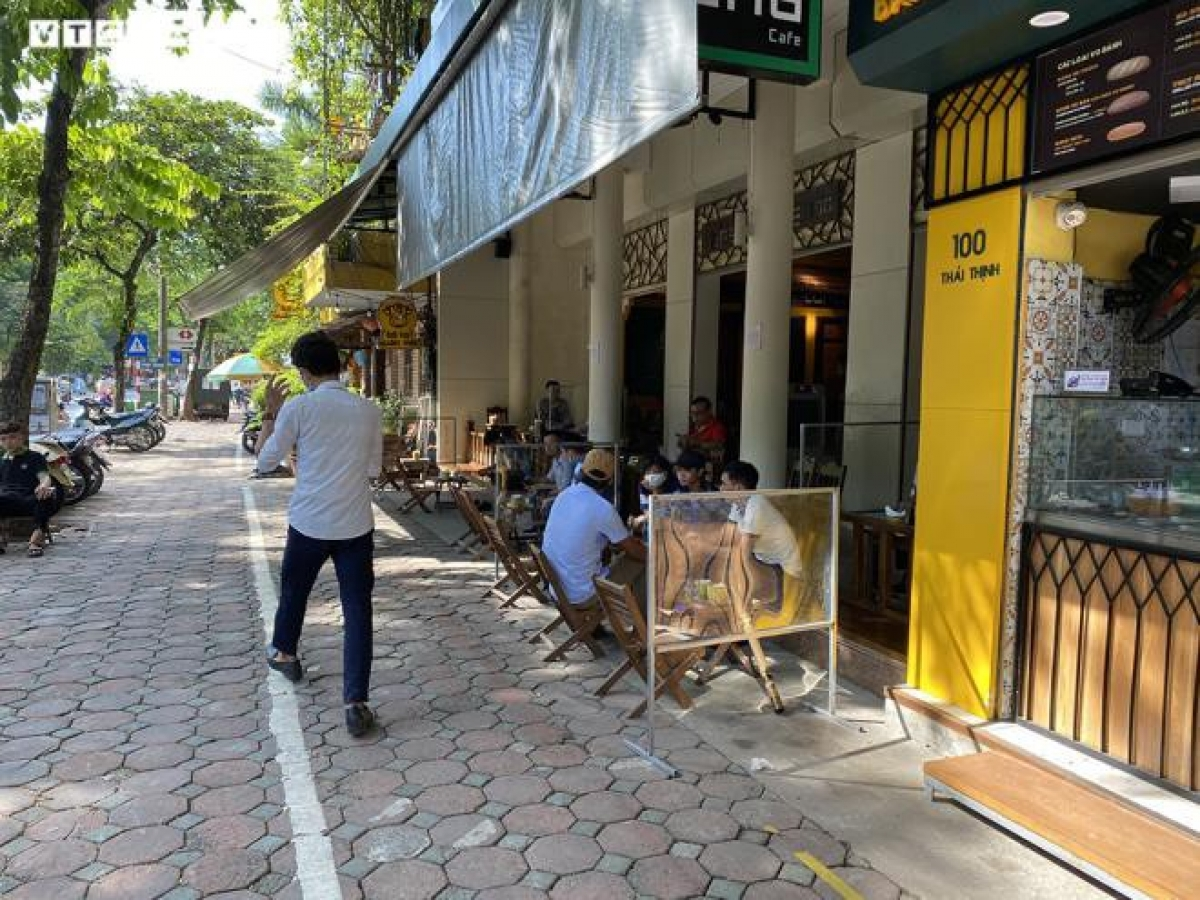 Thay vì sắp xếp các bàn các xa nhau tối thiểu 1 mét, quán cà phê trên đường Thái Thịnh (quận Đống Đa) sử dụng tấm chắn ngăn giọt bắn được đặt giữa các bàn để hạn chế việc tiếp xúc với nhau.