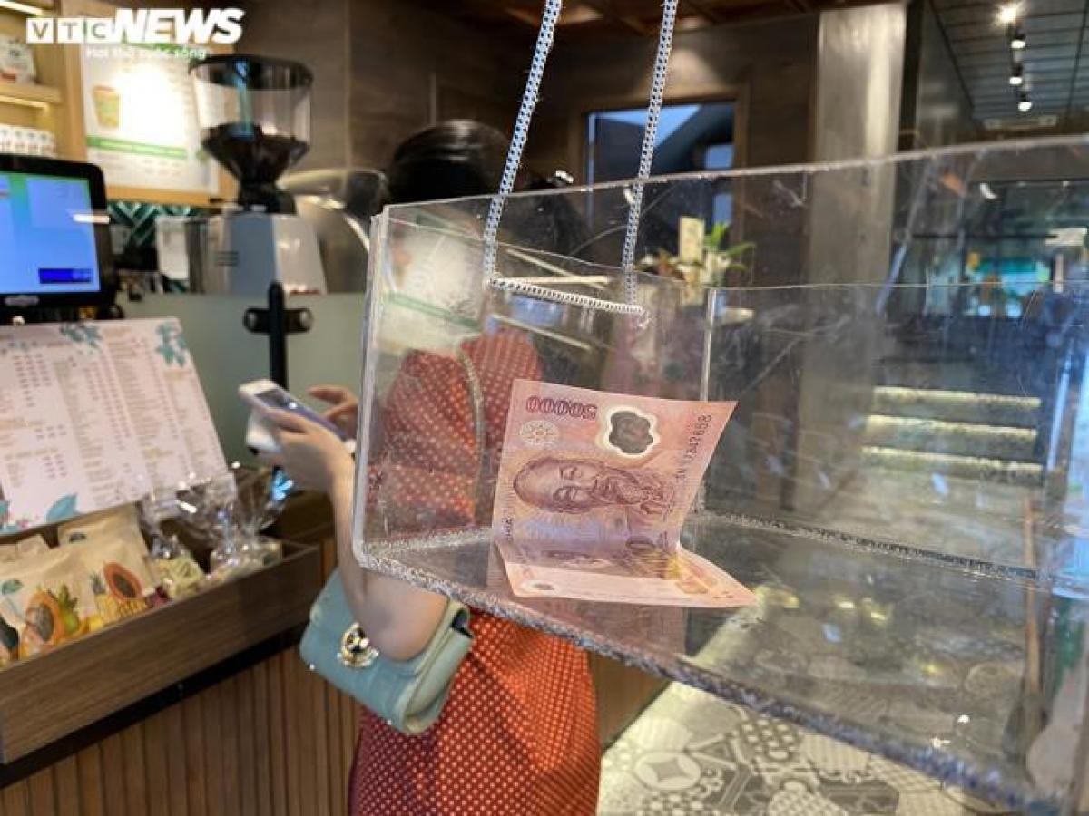 Cửa hàng trà sữa Phúc Long tại phố Trần Đại Nghĩa (quận Hai Bà Trưng) có cách làm độc đáo hơn khi thiết kế ròng rọc để nhận tiền và giao hàng cho khách đối với khách mua mang đi. Cách này sẽ hạn chế được việc tiếp xúc gần của nhân viên bán hàng và khách hàng.