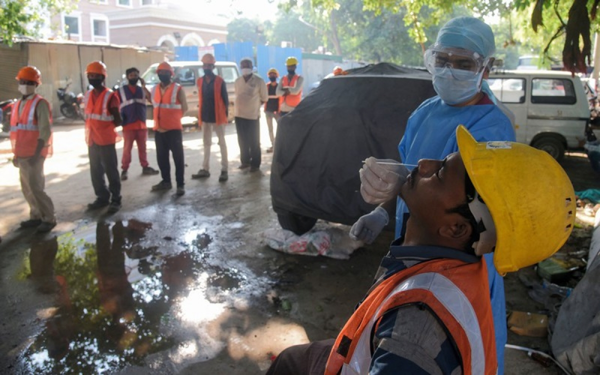 Nhân viên y tế lấy mẫu xét nghiệm Covid-19 với các công nhân xây dựng ở New Delhi. Ảnh: ANI.