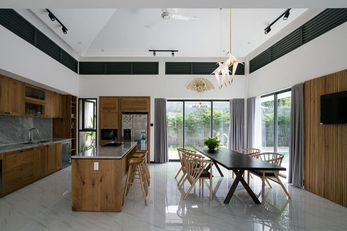 Không gian phòng bếp – ăn rộng thoáng với những ô cửa kính lớn mở ra sân vườn. Màu sắc chủ đạo của nội thất là màu trắng, kết hợp với màu gỗ tự nhiên.