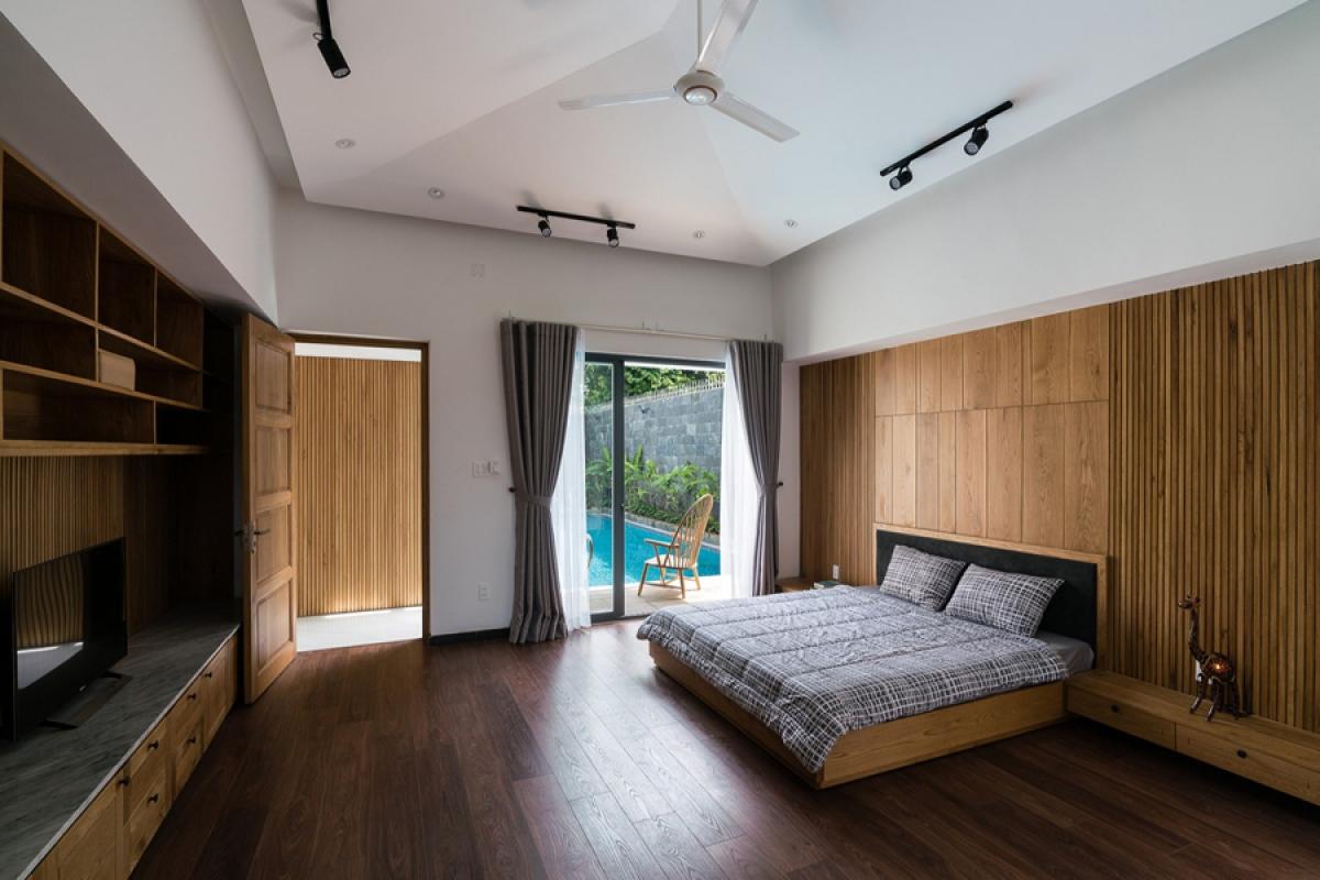 Phòng ngủ chính với ô cửa nhìn ra hồ bơi. Nội thất gỗ tạo cảm giác ấm áp.
