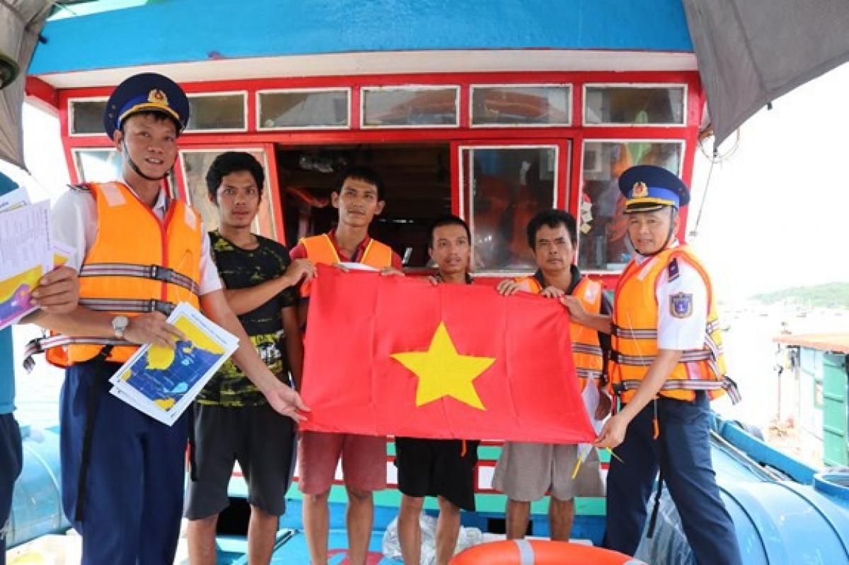Cảnh sát biển tặng cờ Tổ quốc cho ngư dân.