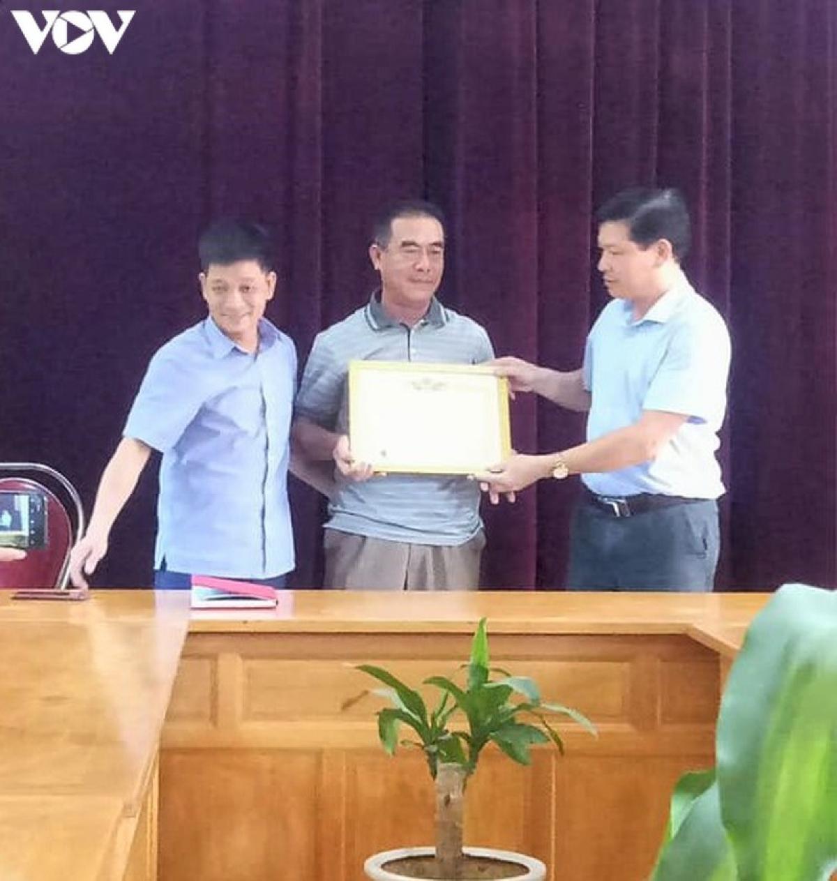 Chủ tịch UBND xã Lang Thíp Lê Minh Lập trao tặng Giấy khen cho ông Dũng (ở giữa).