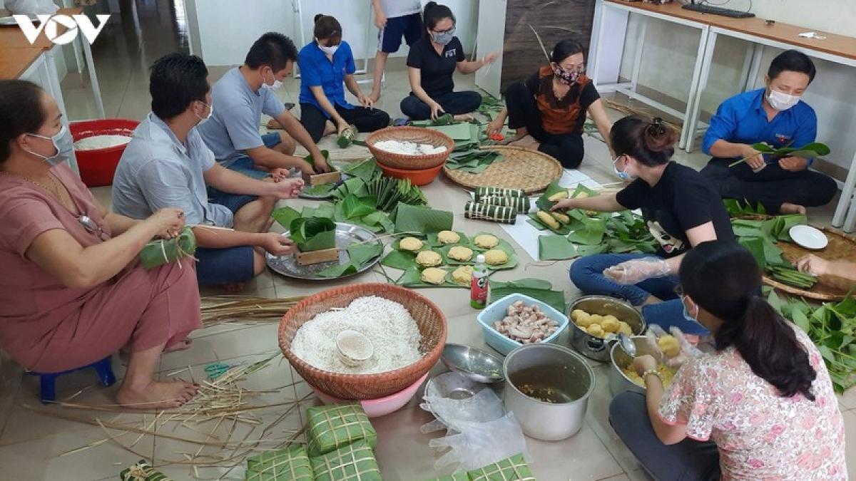Nhiều người dân cùng thực hiện việc gói bánh.