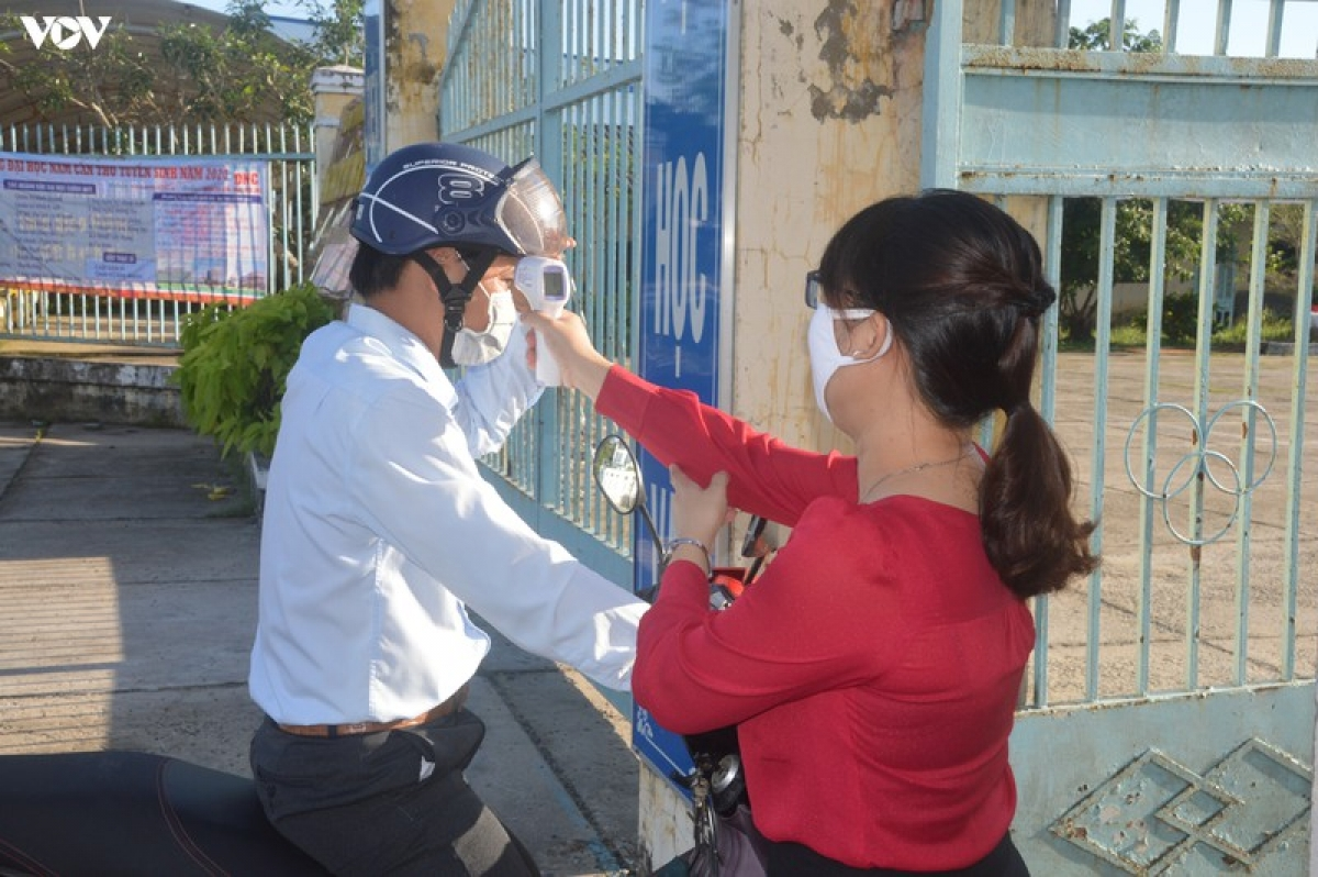 Kiểm tra thân nhiệt cho cán bộ coi thi ở Sóc Trăng.