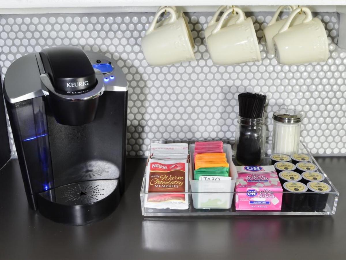 Khu đồ uống: Hãy đựng những gói trà, cà phê và túi đường của bạn trong một cái khay hoặc một hộp đựng trong suốt có ngăn, phân chia rõ các loại đồ để dễ tìm kiếm và sử dụng. Đồng thời, những cốc dùng cho các loại nước này cũng nên được đặt gọn gàng hoặc treo lên ở gần hộp đựng của bạn.