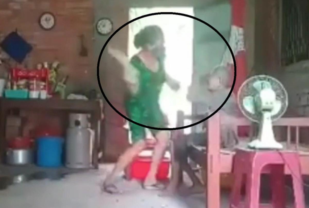 Người con gái liên tục đánh mẹ già (ảnh cắt từ clip)