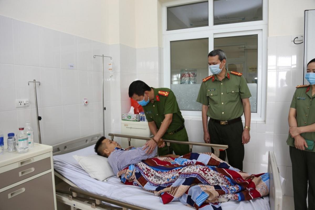 Thượng tá Bùi Quang Bình, Phó Giám đốc Công an tỉnh Quảng Ninh hỏi thăm, động viên Trung úy Trần Quang. Ảnh: Công an Quảng Ninh