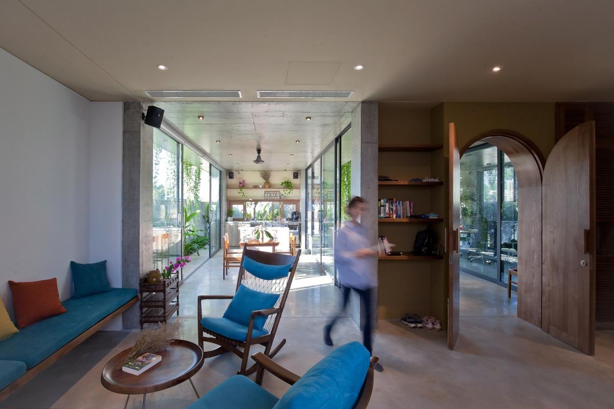Phòng khách giản dị với bộ bàn ghế sofa gỗ, nệm bọc màu xanh mang đến không khí yên bình, dễ chịu.