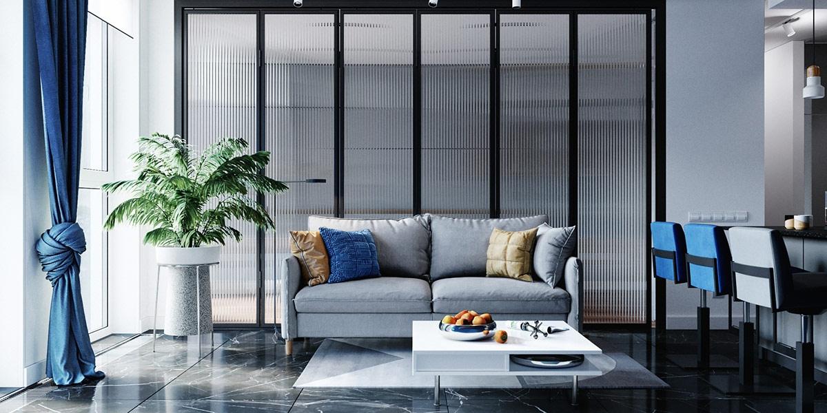 Nội thất phòng khách màu xanh lam, kết hợp điểm nhấn là gối tựa màu vàng và cây xanh trang trí.