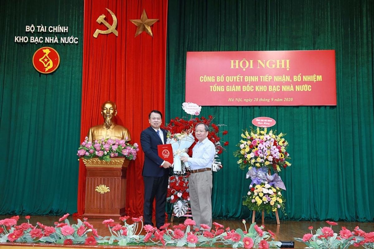 Thứ trưởng Bộ Tài chính trao quyết định cho ông Nguyễn Đức Chi. (Ảnh: KT)