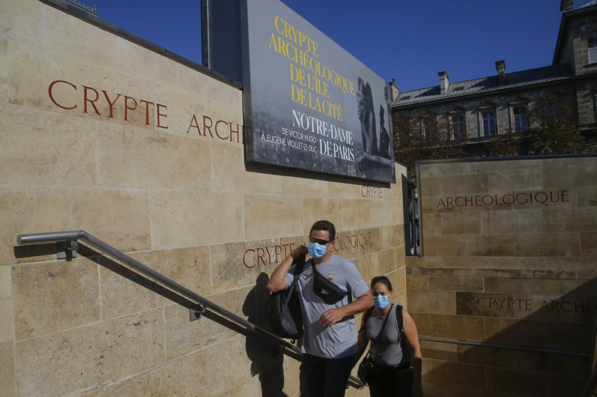 Du khách đeo khẩu trang vào tham quan triển lãm. Ảnh: AP Photo/Michel Euler