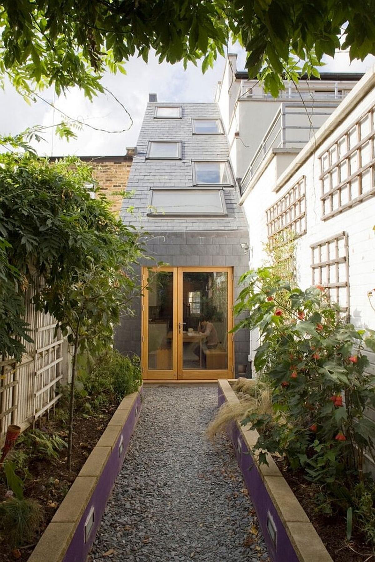 Nôi nhà rộng không quá 2,3 m2. Tuy nhiên bằng tài năng của nhà thiết kế vẫn biến nó trở thành một không gian sống tuyệt vời với đầy đủ các tiện nghi hiện đại.Với ngoại thất màu xám, cùng gỗ và trần dốc đã mang lại cho ngôi nhà vẻ cuốn hút.