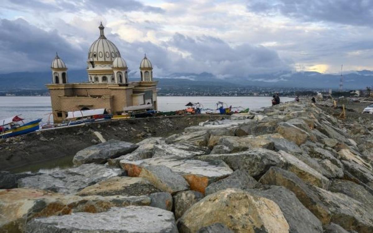 Người dân Palu lặng người trước một nhà thờ bị sóng đánh ra biển. Ảnh: Antara.