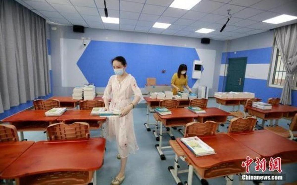 Các cô giáo chuẩn bị sách giáo khóa mới cho học sinh tại một trường học ở Vũ Hán. Ảnh: Chinanews.