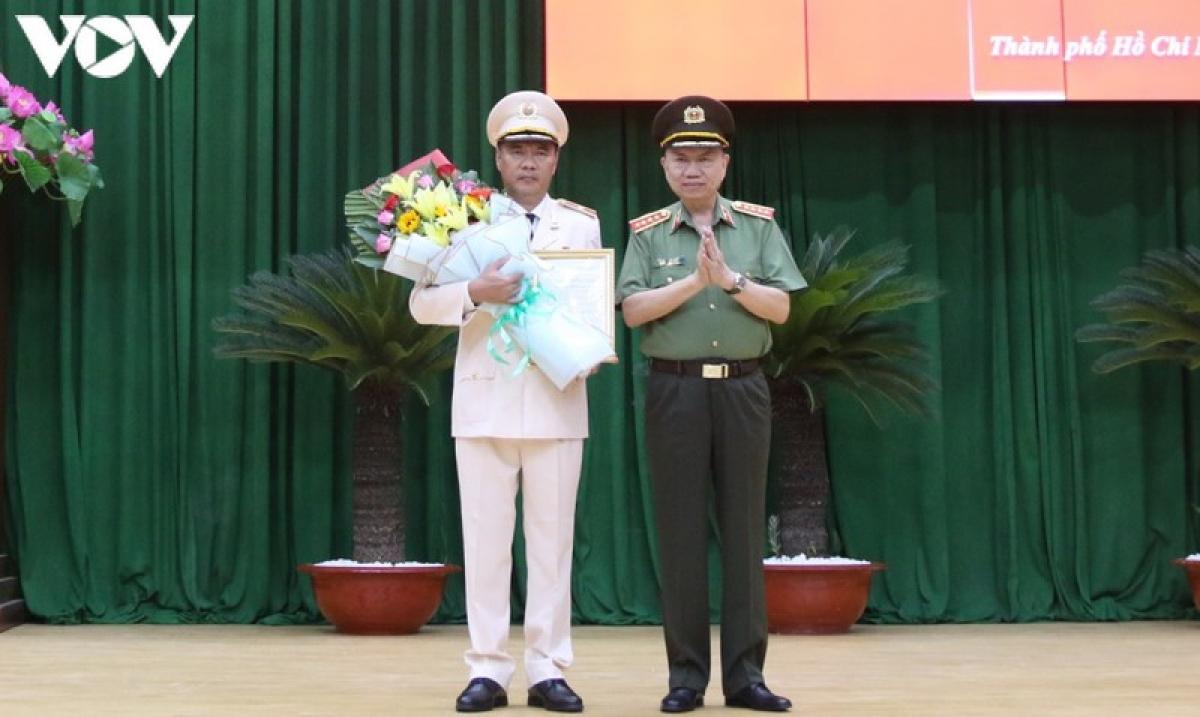 Đại tướng Tô Lâm thừa ủy quyền Chủ tịch nước trao quyết định và tặng hoa chúc mừng Thiếu tướng Cao Đăng Hưng.