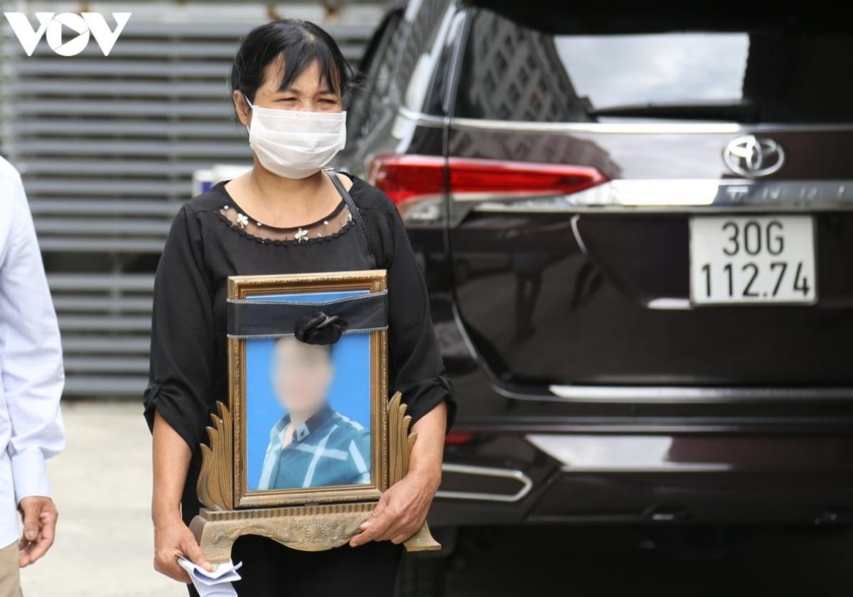 Người nhà mang di ảnh của nạn nhân đến tòa.