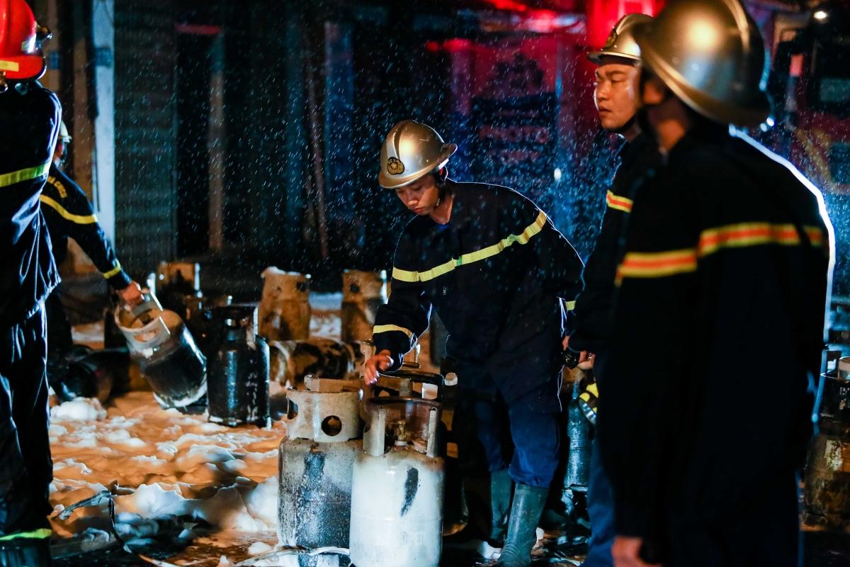 Hiện nguyên nhân vụ việc đang được các cơ quan chức năng điều tra làm rõ. Ảnh: Lực lượng chức năng chuyển những bình ga còn lại sau vụ cháy ra ngoài cơ sở buôn bán ga này.