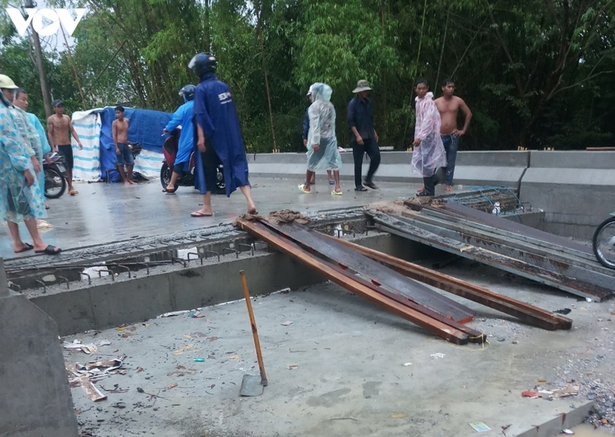 Người dân bắc ván cho các xe máy đi tạm trên cây cầu đang thi công dang dở bên cạnh cầu tạm./.