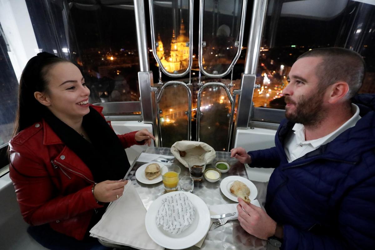 Hai vị khách Hajnalka Lutor và Janos Katus thưởng thức bữa tối trong ca bin đu quay.