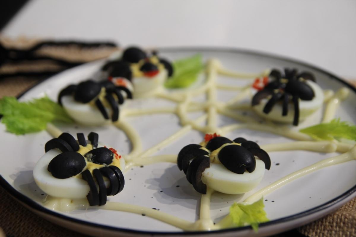 Những chú nhện được tạo hình từ quả oliu nằm ôm trọn nửa quả trứng với phần lòng đỏ trứng đã được nghiền mịn và trộn cùng mù tạt vàng và xốt Mayonnaise Aji-Mayo®.