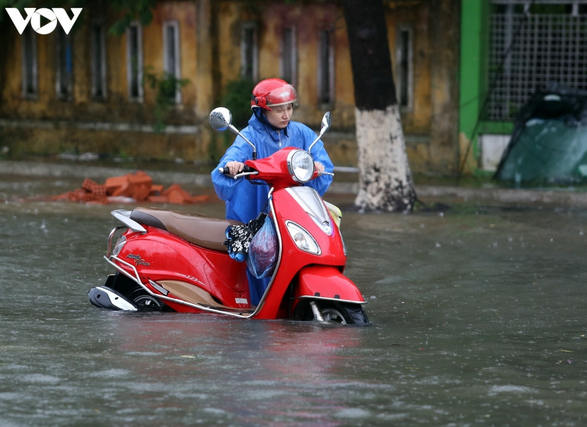 Nhiều người dân gặp khó khi nhiều tuyến đường tại thành phố Tam Kỳ ngập cục bộ. (Ảnh: Xe chết máy giữa trời mưa).