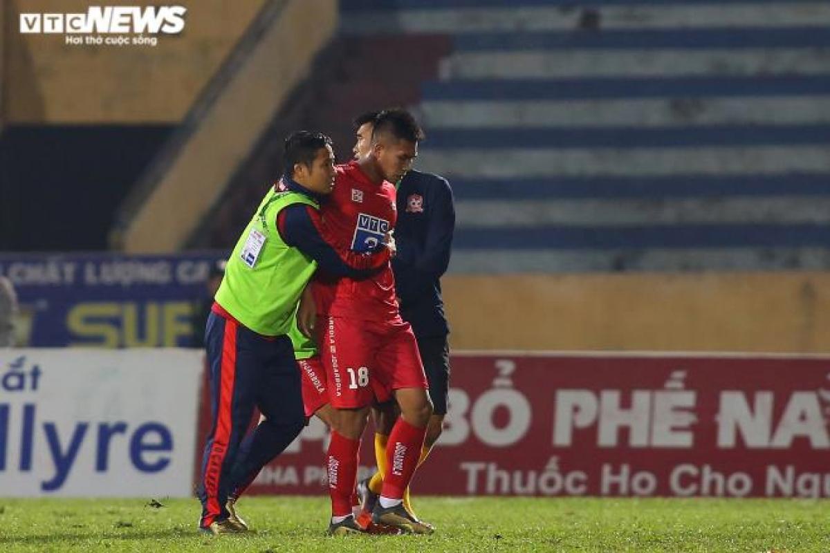Văn Hạnh miễn cưỡng rời sân với sự hộ tống của hai thành viên ban huấn luyện CLB Hải Phòng. HLV Quốc Vượng ôm chặt cầu thủ mang áo số 18 cho đến khi đưa anh ra ngoài sân.