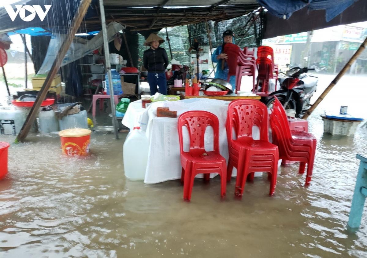 Các hộ buôn bán trên tuyến Quốc lộ 40B, xã Tam Thái, huyện Phú Ninh, tỉnh Quảng Nam dọn đồ đạc vì nước lũ dâng.