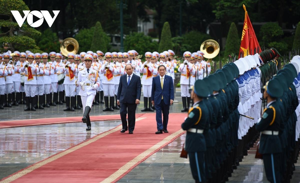 Thủ tướng Nguyễn Xuân Phúc mời Thủ tướng Suga Yoshihide duyệt Đội danh dự Quân đội Nhân dân Việt Nam.