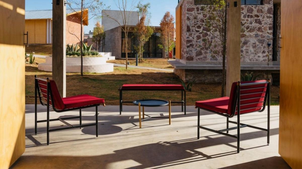 Bộ bàn ghế có đệm màu đỏ đặt ở trước cửa tạo nên một không gian tiếp khách đầy thoáng rộng.