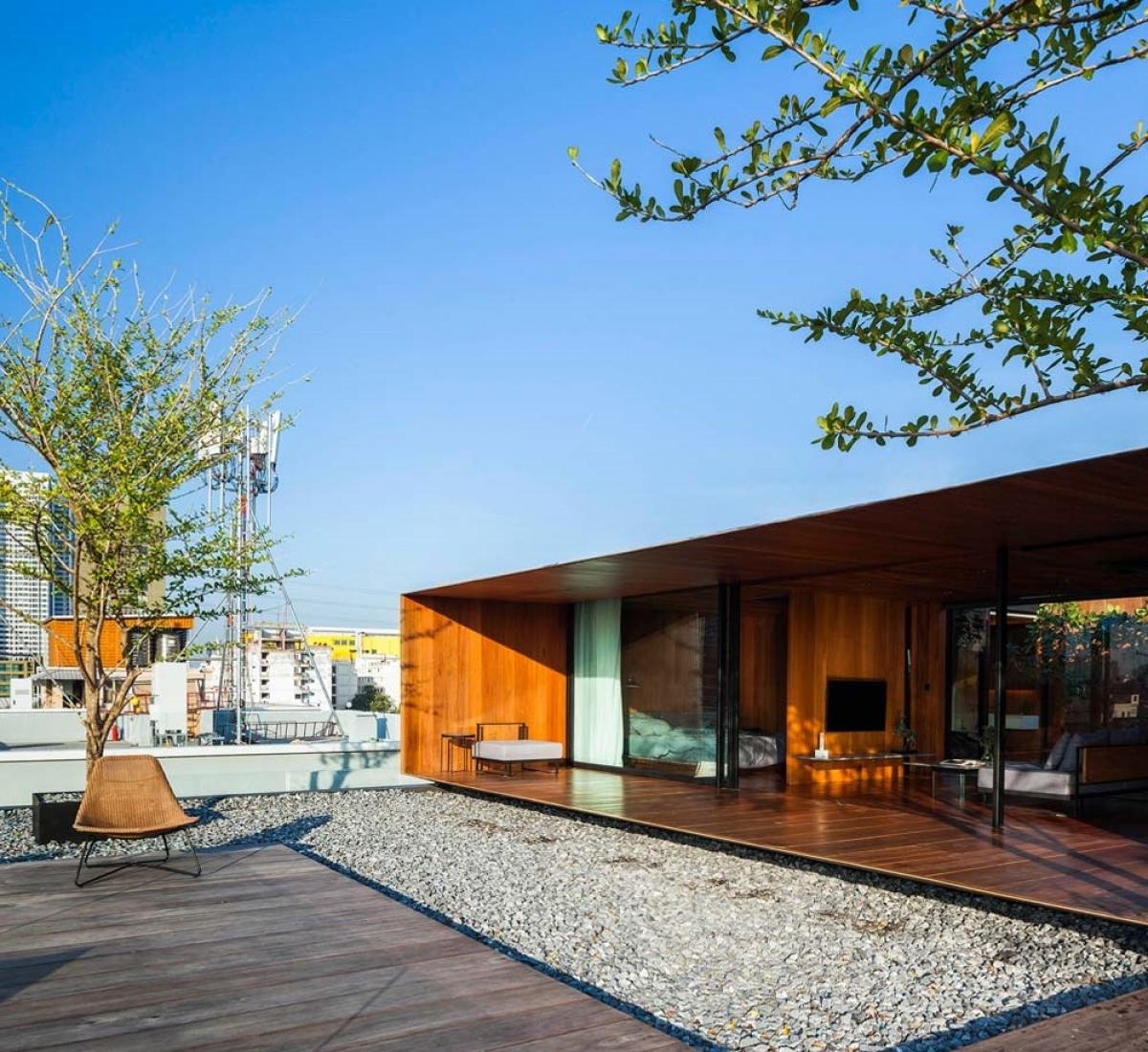 Ngôi nhà nằm trên sân thượng chung cư tầng 5. Với thiết kế theo phong cách hình hộp mang đến người xem một không gian lạ mắt, hiện đại, từ vật liệu chính là gỗ và cây xanh góp phần nên một căn nhà hoàn thiện, ấm áp và trong lành.
