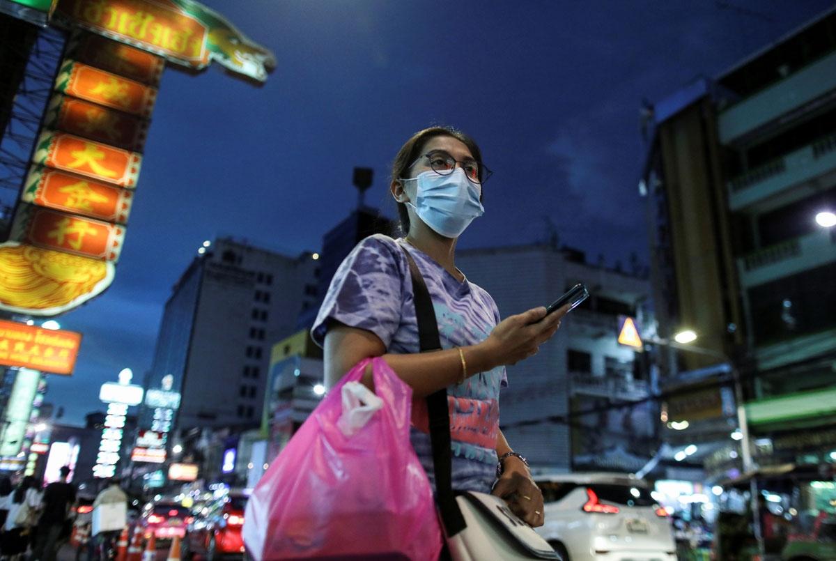 Một phụ nữ đeo khẩu trang phòng chống Covid-19 đang đi trên đường phố Bangkok (Ảnh: Reuters).