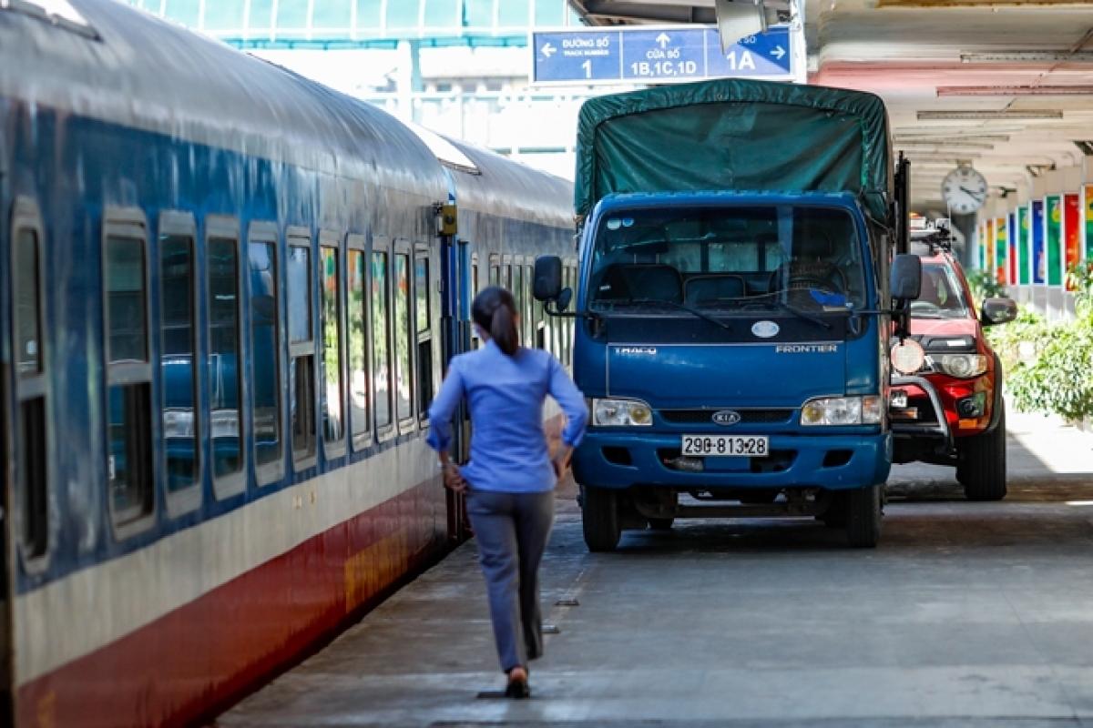 hiều xe tải, xe bán tải và xe cá nhân xếp hàng trong sân ga chờ chuyển hàng.
