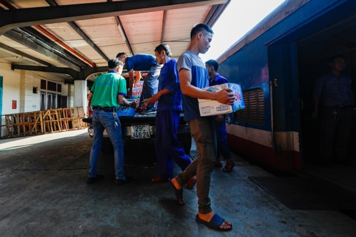 Các công nhân đường sắt vận chuyển hàng hoá từ nhà kho ra toa xe hàng.