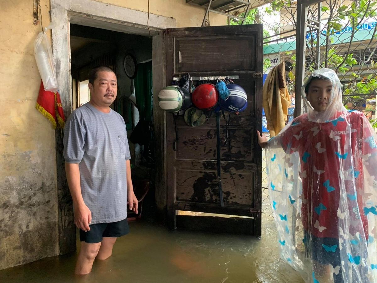 Anh Lê Văn Sơn, ở thôn Thủy Phú, xã Hương Vinh, thị xã Hương Trà dọn dẹp đồ đạc khi nước vào nhà.