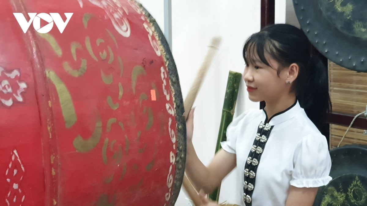A girl learns how to play a drum.