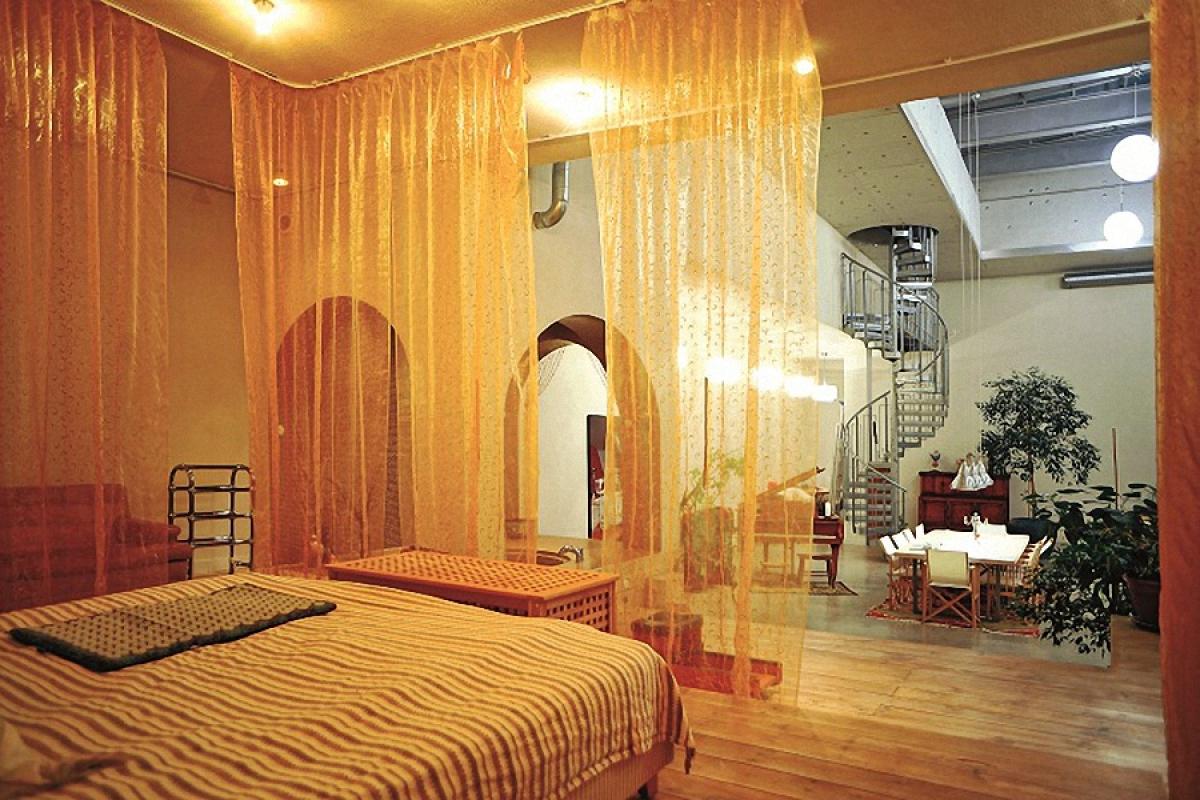 Ranh giới phòng ngủ được ngăn bằng những tấm rèm thưa. Từ phòng ngủ có thể quan sát được cả không gian rộng lớn bên ngoài.