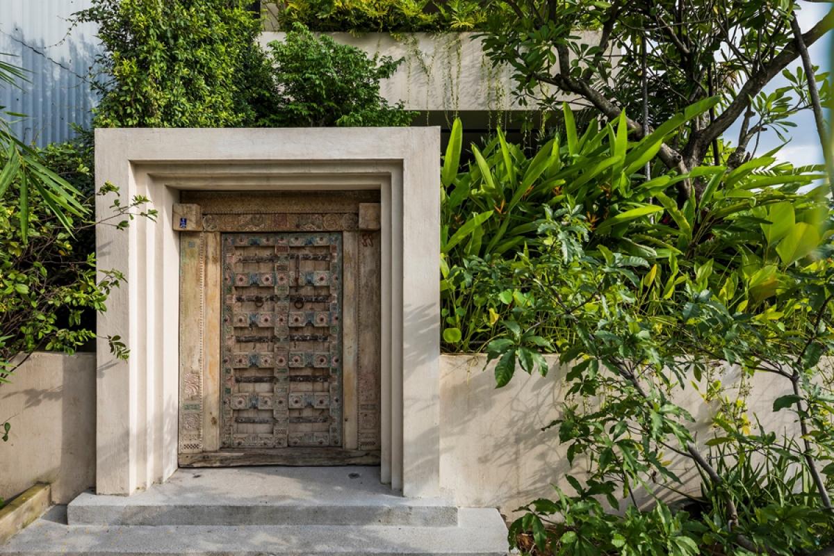 Cổng vào nhà không lớn nhưng ấn tượng bởi hình khối và những cánh cổng được trang trí hoa văn đậm màu sắc Phương Đông.