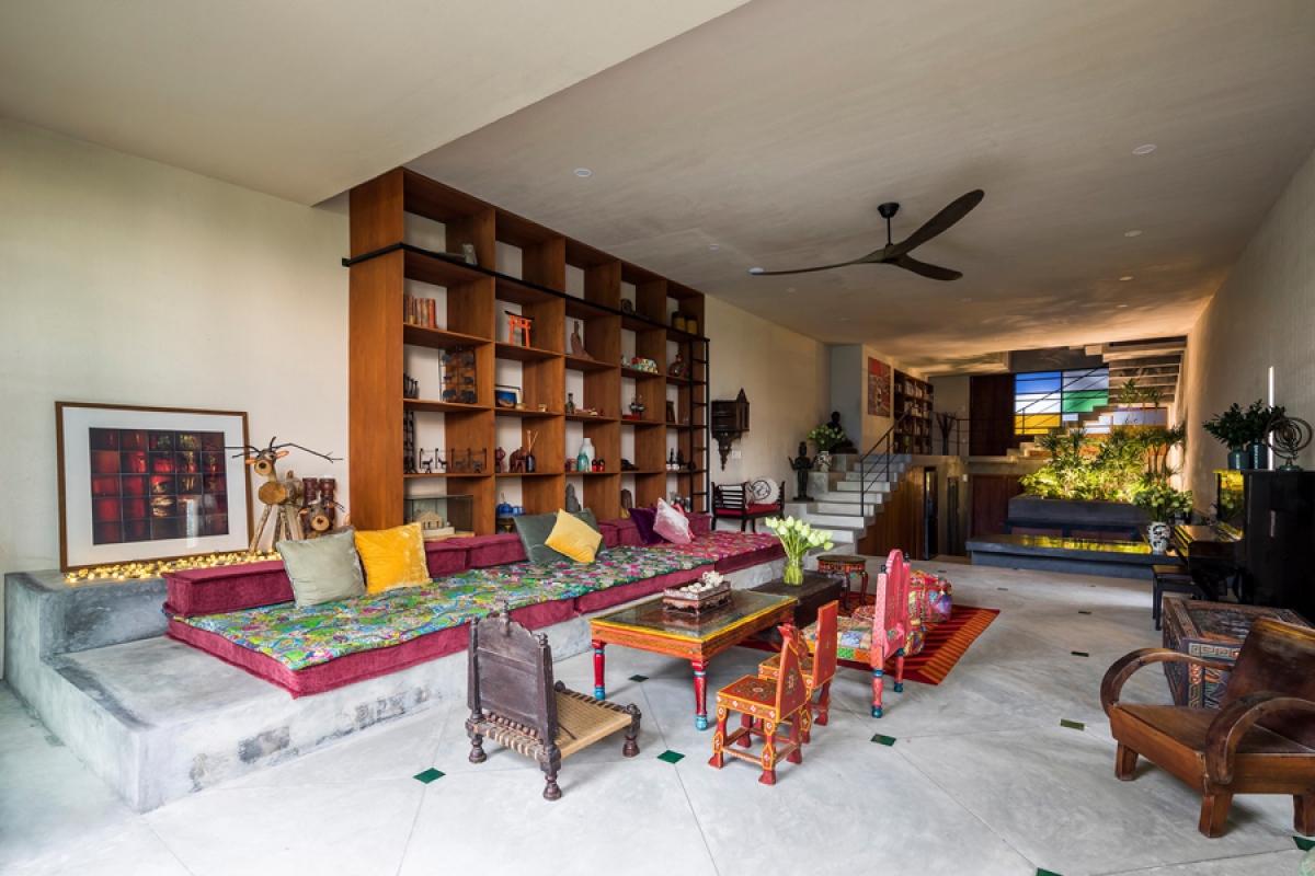 Tầng 1 là một không gian liên hoàn bao gồm phòng khách và bếp – ăn. Vật liệu chủ đạo được sử dụng là bê tông trần mang màu xám đặc trưng.