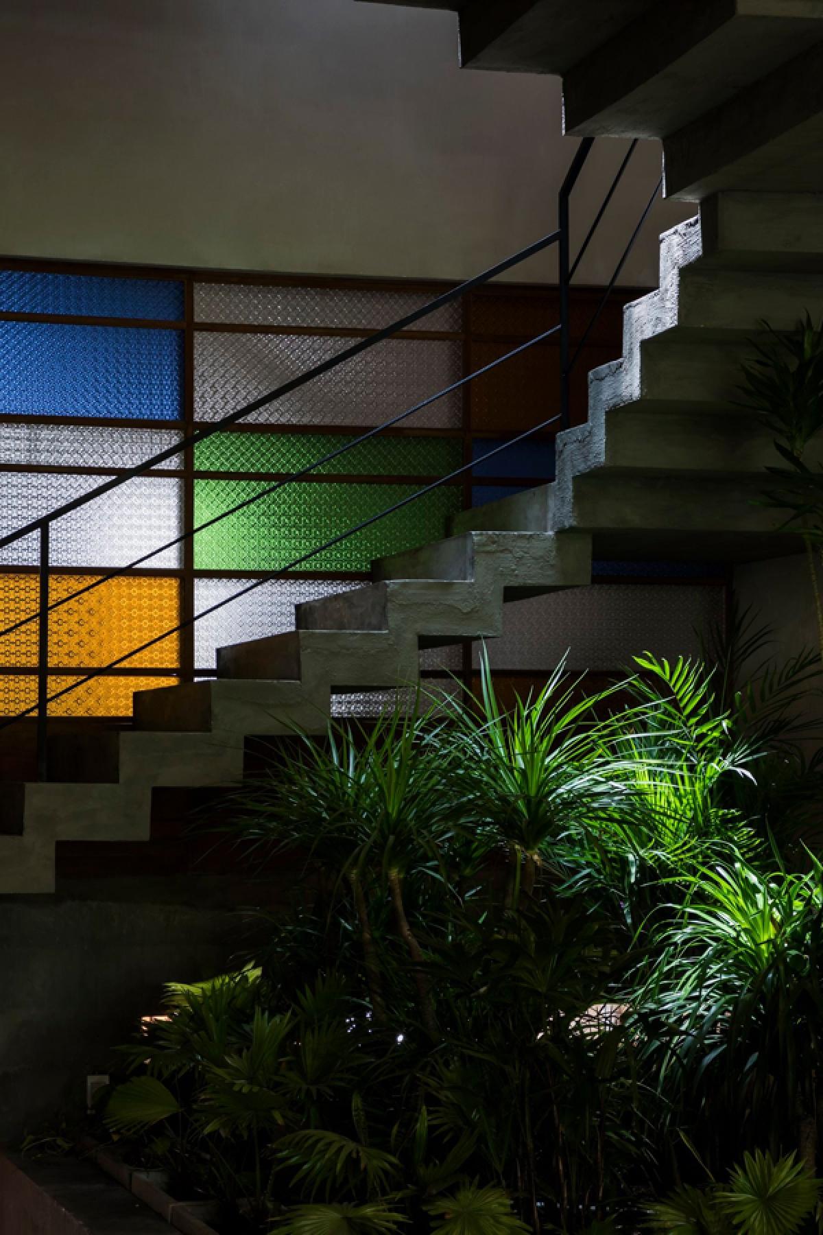 Cầu thang được đổ bê tông nguyên khối, để trần lộ rõ chất liệu thô ráp. Cây xanh và những mảng kính màu làm không gian trở nên sinh động hơn.